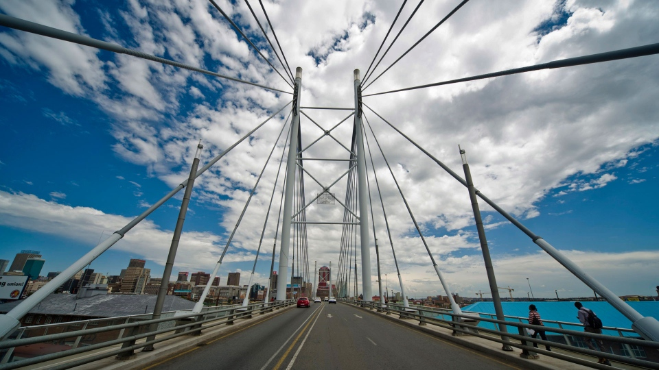 "In this December 2010, file photo, pedestrians cross the Nelson Mandela Bridge into downtown Johannesburg. The blockbuster film ""Black Panther"" has created a new compelling vision of Africa as a continent of smart, technologically savvy people with cool clothes living in a futuristic city amid stunning landscapes. (AP Photo, File)"