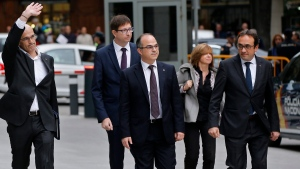 In this Nov. 2, 2017 file photo, fired Catalan Cabinet member Jordi Turull, center, arrives with other former Cabinet members at the national court in Madrid, Spain. The Catalan Parliament speaker has set a Thursday March 22, 2018 vote in the afternoon to elect as the next regional president, a former separatist minister who could be indicted on rebellion charges only one day after. (AP Photo/Paul White, File)