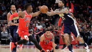 Chicago Bulls' David Nwaba (11) and Denver Nuggets' Wilson Chandler reach for the ball during the second half of an NBA basketball game Wednesday, March 21, 2018, in Chicago. (AP Photo/Charles Rex Arbogast)
