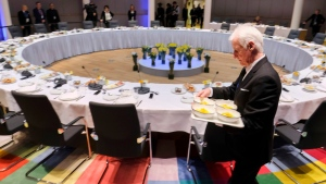 A worker sets out plates during a breakfast meeting at an EU summit in Brussels on Friday, March 23, 2018. Leaders from the 28 European Union nations meet for a second day of an EU summit to assess the state of Brexit negotiations and the prospect of a trade war with the United States. (Olivier Hoslet, Pool Photo via AP)