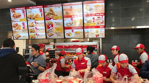 Workers serve customers at Jollibee's Toronto location, on Sunday, April 1, 2018.