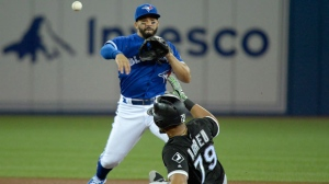 Toronto Blue Jays second baseman Devon Travis (29) forces out Chicago White Sox first baseman Jose Abreu (79) at second base before turning a double play during fourth inning American League baseball action in Toronto on Monday, April 2, 2018. THE CANADIAN PRESS/Nathan Denette