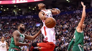 Toronto Raptors guard Kyle Lowry (7) is fouled by Boston Celtics forward Jayson Tatum (right) as he goes to the basket by guard Kadeem Allen (left) during second half NBA basketball action in Toronto on Wednesday, April 4, 2018. THE CANADIAN PRESS/Frank Gunn