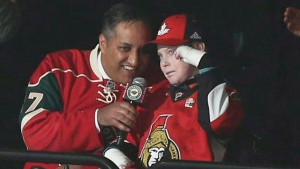 """Canadians Consul General Khawar Nasim, center left, and Jonathan Pitre, right, help with the call out the """"Let's Play Hockey"""" arena tradition prior to the start of an NHL hockey game with the Minnesota Wild against Ottawa Senators, Thursday, March 30, 2017, in St. Paul, Minn. THE CANADIAN PRESS/AP-Stacy Bengs"""