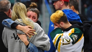 Mourners comfort each other as people attend a vigil at the Elgar Petersen Arena, home of the Humboldt Broncos, to honour the victims of a fatal bus accident in Humboldt, Sask. on Sunday, April 8, 2018. THE CANADIAN PRESS/Jonathan Hayward
