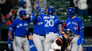 Toronto Blue Jays' Josh Donaldson (20) celebrates his grand slam with teammates Curtis Granderson, left, Kevin Pillar, right, and others as Baltimore Orioles catcher Caleb Joseph, bottom front, looks on during the ninth inning of a baseball game, Monday, April 9, 2018, in Baltimore. (AP Photo/Nick Wass)