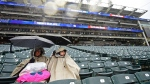 Annette and Kaden Decker sit as they wait out a rain delay in a baseball game between the Cleveland Indians and the Toronto Blue Jays, Saturday, April 14, 2018, in Cleveland. (AP Photo/David Dermer)