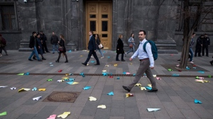People walk past paper airplanes that were thrown by protesters in front of the building of the Federal Security Service in Lubyanskaya Square in Moscow, Russia, Monday, April 16, 2018. Russia's communications watchdog said Monday it has begun enforcing a nationwide ban for the popular messaging app Telegram. (AP Photo/Pavel Golovkin)
