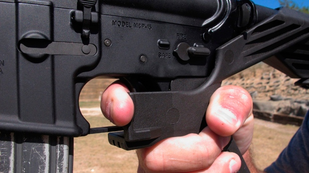 """In this Oct. 4, 2017, file photo, shooting instructor Frankie McRae demonstrates the grip on an AR-15 rifle fitted with a """"bump stock"""" at his 37 PSR Gun Club in Bunnlevel, N.C. The largest manufacturer of bump stocks, which allow semi-automatic weapons to fire rapidly like automatic firearms, announced Wednesday, April 18, 2018, that it will stop taking orders and shut down its website next month. (AP Photo/Allen G. Breed, File)"""
