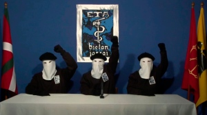 In this file image made from video provided on Oct. 20, 2011, masked members of the Basque separatist group ETA raise their fists in unison following a news conference at an undisclosed location. In a statement published on Friday April 20, 2018, the Basque militant group ETA says it is sorry for the pain that its armed campaign for Basque independence caused, and vows not to fall back into violence. (Gara via AP, File)