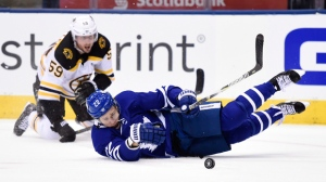 Toronto Maple Leafs defenceman Nikita Zaitsev (22) and Boston Bruins centre Tim Schaller (59) battle for the puck during third period NHL round one playoff hockey action in Toronto on Thursday, April 19, 2018. THE CANADIAN PRESS/Nathan Denette