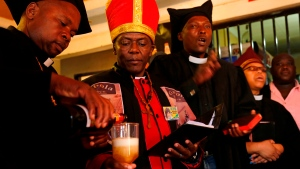 Leader of the Gabola Church, self-proclaimed Pope, Tsietsi Makiti, second left, prepares to baptize newcomers to this church during a service in a bar in Orange Farm, south of Johannesburg Sunday, April 15, 2018. The new church in South Africa celebrates drinking alcohol and holds enthusiastic, alcohol fuelled services in bars, for those who have been rejected by other churches because they drink alcohol. (AP Photo/Denis Farrell)
