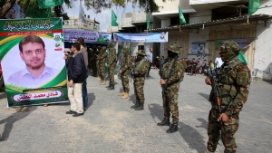 Relatives sit up a photo while masked militants from the Izzedine al-Qassam Brigades, a military wing of Hamas, receive condolences at the house mourning of engineer Fadi al-Batsh, who was killed assassinated in Malaysia this morning, in front of his family house in Jebaliya, Gaza Strip, Saturday, April 21, 2018. Gaza's ruling Hamas militant group said Saturday that a man who was gunned down in Malaysia was an important member of the organization, raising suspicions that Israel was behind the brazen killing. (AP Photo/Adel Hana)