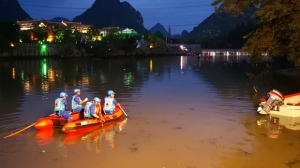 Rescuers search for missing boaters on the Taohua River in Guilin in southern China's Guangxi Zhuang Autonomous Region, Saturday, April 21, 2018. Chinese state media said that several people have died and others are missing after two dragon boats capsized in southern China, causing dozens of people to fall into the water. (Chinatopix via AP)
