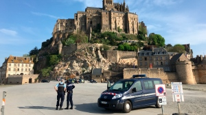 Police attend the scene of an evacuation at Mont Saint-Michel, on France's northern coast, Sunday April 22, 2018. Authorities are evacuating tourists and others from the Mont-Saint-Michel abbey and monument in western France after a visitor apparently threatened to attack security services. (Denis Surfys via AP)