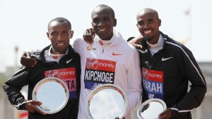 Eluid Kipchoge of Kenya placed first, centre, Tola Shura Kitata of Ethiopia placed second, left, and Mo Farah of Britain placed third, right, during presentations for the Men's race in the London Marathon in London, Sunday, April 22, 2018. (AP Photo/Kirsty Wigglesworth)