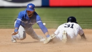 New York Yankees' Aaron Hicks, right, steals second base while Toronto Blue Jays shortstop Lourdes Gurriel tries to field a bad throw from catcher Russell Martin during the seventh inning of a baseball game at Yankee Stadium, Sunday, April 22, 2018, in New York. Gurriel count not control the ball and Hicks advanced to third base. (AP Photo/Seth Wenig)