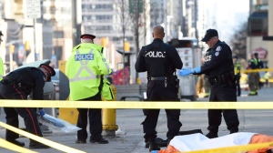Police secure an area around a covered body in Toronto after a van mounted a sidewalk crashing into a number of pedestrians on Monday, April 23, 2018. THE CANADIAN PRESS/Nathan Denette