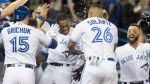 Toronto Blue Jays' Curtis Granderson mobbed by teammates after he hit a walk off home run to beat the Boston Red Sox in the 10th inning American League MLB baseball game action in Toronto on Tuesday April 24, 2018. THE CANADIAN PRESS/Fred Thornhill