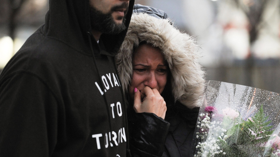 A woman cries at a vigil on Yonge Street in Toronto, Tuesday, April 24, 2018. Ten people were killed and 14 were injured in Monday's deadly attack in which a van struck pedestrians in northern Toronto. THE CANADIAN PRESS/Galit Rodan