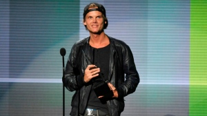 """In this Nov. 24, 2013 file photo, Avicii accepts the award for favorite artist - electronic dance music at the American Music Awards in Los Angeles. Avicii's family released a statement Monday, April 23, 2018, saying they """"would like to thank you for the support and the loving words about our son and brother.'"""" They say they are grateful for his fans around the world who loved his music. Swedish-born Avicii, whose name is Tim Bergling, was found dead, April 20, in Muscat, Oman. He was 28. (Photo by John Shearer/Invision/AP, File)"""