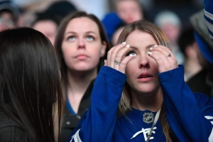 Amanda Allan reacts as she watches the Toronto Maple Leafs play the Boston Bruins on a large TV screen at Maple Leaf Square in Toronto, Wednesday, April 25, 2018. The Bruins stormed back to defeat the Toronto Maple Leafs 7-4 on Wednesday in Game 7 to advance to the second round of the Stanley Cup playoffs. THE CANADIAN PRESS/Galit Rodan