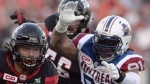 Ottawa Redblacks' Kienan Lafrance (27) makes his way past Montreal Alouettes' Alan-Michael Cash (91) during first half CFL action on Friday, Aug. 19, 2016 in Ottawa. The Toronto Argonauts have signed international defensive tackle Cash. THE CANADIAN PRESS/Justin Tang