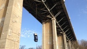 A vehicle is seen dangling from a bridge near the Don Valley Parkway. (Cam Woolley/ CP24)