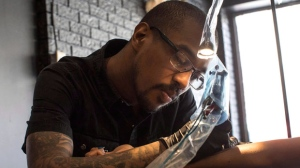 Tattoo artist D.C Nchama works on Shar Charlatan's Black Panther tattoo at Funky Inc. Tattoo, in Toronto on Saturday, March 31, 2018. THE CANADIAN PRESS/Chris Young