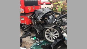 In this Friday, May 11, 2018, photo released by the South Jordan Police Department shows a traffic collision involving a Tesla Model S sedan with a Fire Department mechanic truck stopped at a red light in South Jordan, Utah. (South Jordan Police Department via AP)