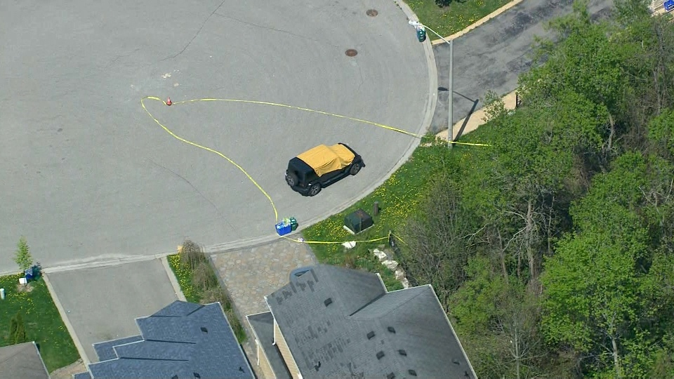 A tarp is seen drawn over the front of Jeep where a man was found dead on May 17, 2018. (Chopper 24)