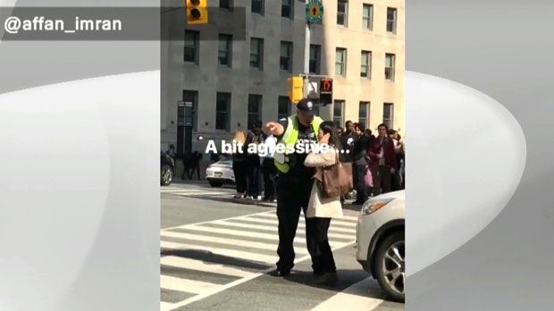 A cop is seen becoming agitated with a female pedestrian at a downtown intersection. (Twitter / @affan_imran)