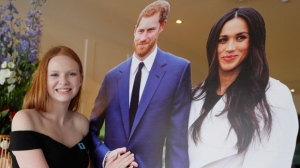 "Faith Dickinson, 15, from Peterborough, Ont. poses with cutouts of Prince Harry and Meghan Markle in Windsor, England on Friday, May 18, 2018. Teenage royal wedding guest Dickinson says she's got her ""dream dress"" ready for the wedding. THE CANADIAN PRESS/Kirsty Wigglesworth"