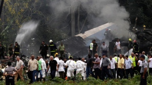 Cuba's President Miguel Diaz-Canel, third from left, walks away from the site where a Boeing 737 plummeted into a yuca field with more than 100 passengers on board, in Havana, Cuba, Friday, May 18, 2018. The Cuban airliner crashed just after takeoff from Havana's international airport on Friday. (AP Photo/Enrique de la Osa)