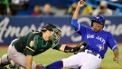 Toronto Blue Jays' Curtis Granderson, right, is tagged out at home plate by Oakland Athletics catcher Josh Phegley (19) during first inning American League baseball action in Toronto on Friday, May 18, 2018. THE CANADIAN PRESS/Frank Gunn