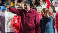 Venezuela's President Nicolas Maduro and his wife Cilia Flores wave to supporters at the presidential palace in Caracas, Venezuela, Sunday, May 20, 2018. Venezuela's election officials say the socialist leader won a second six-year term, while his main rivals are disputing the legitimacy of the vote and calling for a new election. (AP Photo/Ariana Cubillos)