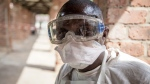 In this photo taken Saturday, May 12, 2018, a health worker wears protective clothing outside an isolation ward to diagnose and treat suspected Ebola patients, at Bikoro Hospital in Bikoro, the rural area where the Ebola outbreak was announced last week, in Congo. (Mark Naftalin/UNICEF via AP)