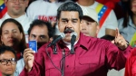Venezuela's President Nicolas Maduro, holding a copy of the country's constitution, addresses supporters at the presidential palace in Caracas, Venezuela, after electoral officials declared he was re-elected on Sunday, May 20, 2018. (AP Photo/Ariana Cubillos)