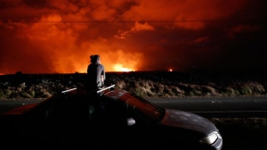 In this May 19, 2018 file photo, Brittany Kimball watches as lava erupts from a fissure near Pahoa, Hawaii. White plumes of acid and extremely fine shards of glass billowed into the sky over Hawaii as molten rock from Kilauea volcano poured into the ocean, creating yet another hazard from an eruption that began more than two weeks ago: A toxic steam cloud. (AP Photo/Jae C. Hong, file)