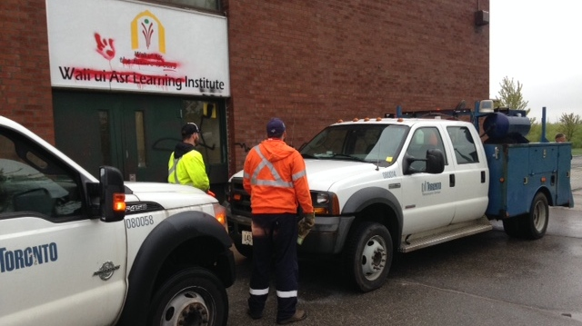 Crews work to clean up graffiti spray-painted on a Muslim school in Scarborough. (Cam Woolley/ CP24)
