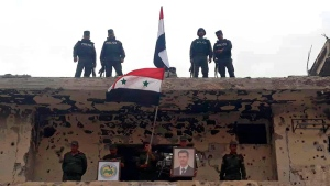 In this photo released by the Syrian official news agency SANA, Syrian military and police forces fly their national flags on a damaged building and hold a picture of Syrian President Bashar Assad, in the Hajar al-Aswad neighborhood, southern Damascus, Syria, Tuesday, May 22, 2018. Syrian state TV said Tuesday the military and police forces are celebrating recapturing the last neighborhoods in Damascus that were held by the rebels and the Islamic State group. (SANA via AP)