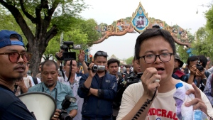 Thai pro-democracy leader Anon Nampa, right speaks during a protest march to mark the fourth anniversary of the military take-over of government in Bangkok, Thailand, Tuesday, May 22, 2018. Police in the Thai capital deployed about 3,200 officers to block a march by about 200 demonstrators, and arrested several leaders including Nampa for protesting four years of military rule and calling for elections this year. (AP Photo/Gemunu Amarasinghe)