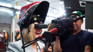 Ontario NDP leader Andrea Horwath, left, tests out a virtual reality welding device as she makes a campaign stop talking with apprentices and journeymen at the Ironworkers local 721 office in Toronto on Tuesday, May 22, 2018. THE CANADIAN PRESS/Nathan Denette