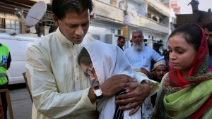 Abdul Aziz Sheikh, father of Sabika Sheikh, the Pakistani exchange student killed in a mass shooting at a high school in Texas, comforts Sabika's friends outside his home prior to her funeral prayer in Karachi, Pakistan, Wednesday, May 23, 2018. (AP Photo/Fareed Khan)