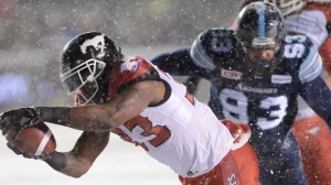 Calgary Stampeders running back Jerome Messam (33) dives into the end zone for a touchdown ahead of Toronto Argonauts defensive tackle Linden Gaydosh (93) during first half CFL football action in the 105th Grey Cup Sunday November 26, 2017 in Ottawa. THE CANADIAN PRESS/Ryan Remiorz