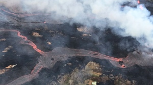 This Wednesday, May 23, 2018 photo shows a helicopter overflight of a volcano near Pahoa, Hawaii. The volcano produces methane when hot lava buries and burns plants and trees. Scientists say the methane can seep through cracks several feet away from the lava. ( U.S. Geological Survey via AP)