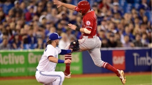 Los Angeles Angels' Zack Cozart is tagged out at third by Toronto Blue Jays third baseman Josh Donaldson (20) during sixth inning American League baseball action in Toronto on Wednesday, May 23, 2018. THE CANADIAN PRESS/Frank Gunn