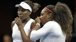 In this Feb. 11, 2018, file photo, USA's Venus Williams, left, and Serena Williams , right, talk between points in their doubles match against Netherlands' Leslie Herkhove and Demi Schuurs in the first round of Fed Cup tennis competition in Asheville, N.C. (AP Photo/Chuck Burton, File)