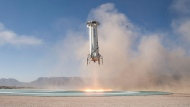 In this Tuesday, Dec. 12, 2017 photo provided by Blue Origin, the New Shepard booster lands in west Texas during a test.  (Blue Origin via AP)