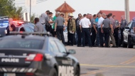 Police and emergency personnel surround the scene of a shooting at Lake Hefner in Oklahoma City, Thursday, May 24, 2018. A man armed with a pistol walked into Louie's On The Lake restaurant at the dinner hour and opened fire, wounding two customers, before being shot dead by a handgun-carrying civilian in the parking lot, police said. (Bryan Terry/The Oklahoman via AP)